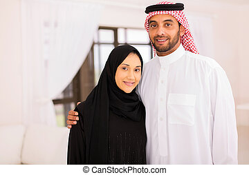 muslim couple at home - close up portrait of happy muslim...