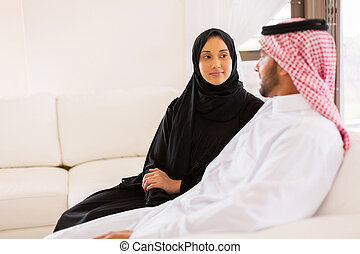 young muslim couple sitting on sofa - lovely young muslim...