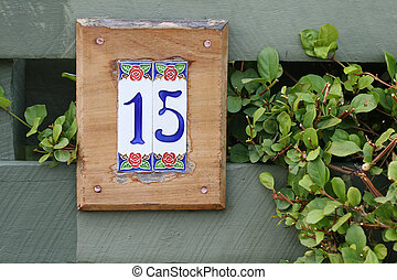 tiled number fifteen sign for home against green fence with...