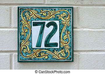 tiled number seventy two sign for home against cream brick...