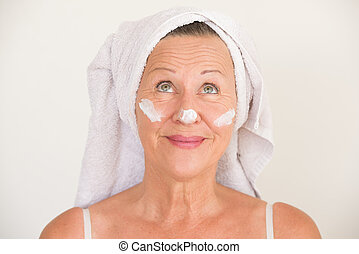 Mature Woman with moisturizer on face - Portrait attractive...