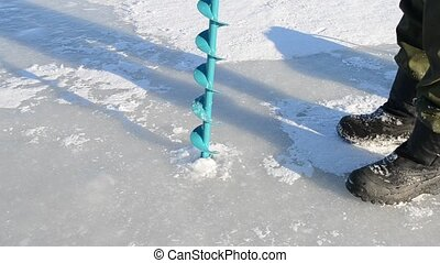 Fisherman and ice screws - Drilling of ice fishing ice...