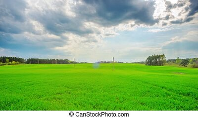 Green field and storm clouds, panoramic time-lapse