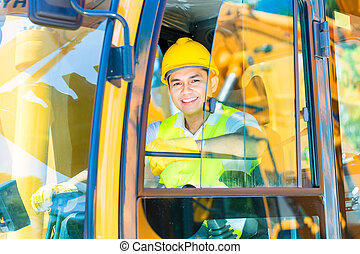 Asian shovel excavator driver on construction site - Asian...