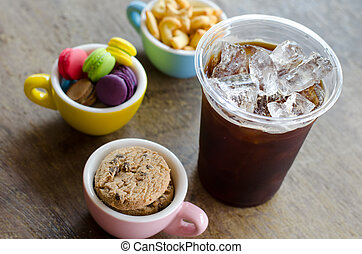 black ice coffee and dessert in cup on wooden background