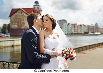 Wedding couple on riverside - Wedding couple kissing on the...