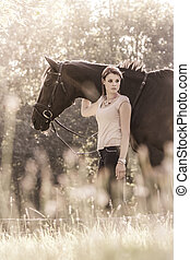 Vintage young equestrian woman with horse in summer sun...