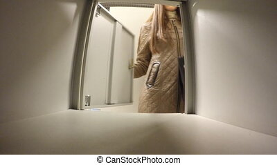 Woman puts the bag in a locker storage chamber.