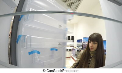 Young woman is looking for a new refrigerator in an...
