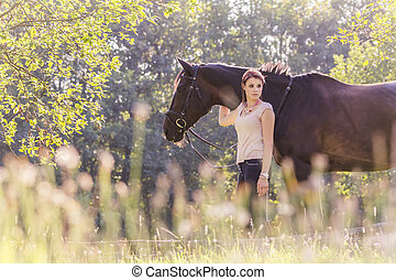 Beautiful young equestrian woman with horse in summer sun...