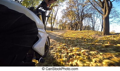 Motorcycle riding the forest road on a sunny autumn day
