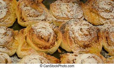 Sifting icing sugar onto buns - Sifting powder sugar onto...