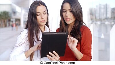 Young woman looking at a tablet outdoors - Two attractive...