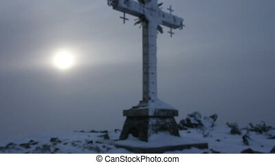 Cross at Mustag mountain top in winter day, Russia, Siberia