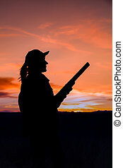 Hunter Silhouetted at Sunset - a woman hunter silhouetted at...