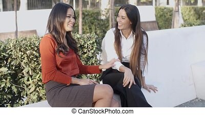 Vivacious young women sitting outdoors laughing - Vivacious...