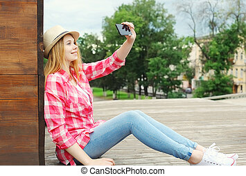 Pretty cool girl taking picture self portrait on smartphone in city