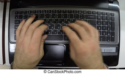 Man hands typing on a notebook laptop keyboard .
