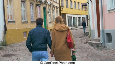 Loving couple having a walk in old empty street - Back shot...