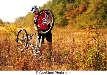 Man cyclist repairing a bike against green nature - cyclist...