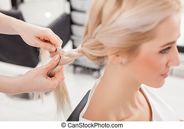 Cheerful hairdresser is braiding human blond hair - Close up...