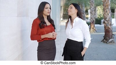 Two women friends standing chatting outdoors in an urban...
