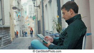 Adult Man With Tablet Computer Sitting In The Street -...