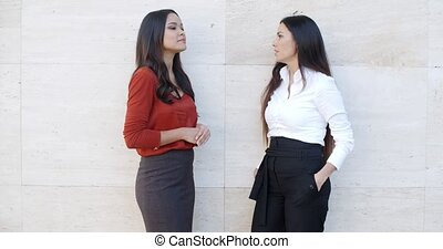 Two chic young women standing chatting - Two chic relaxed...