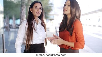 Two natural young woman standing talking outdoors in a high...