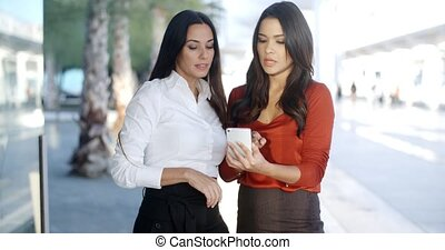 Two pretty stylish women reading an sms or text message on a...
