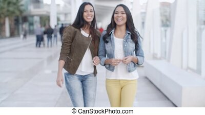 Two young women strolling down a promenade - Two young women...