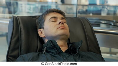 Man having a rest in massage chair - Close-up shot of a man...