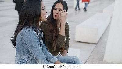 Two trendy young women relaxing on a white bench on a city...