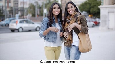 Happy young women waving at the camera - Two trendy happy...