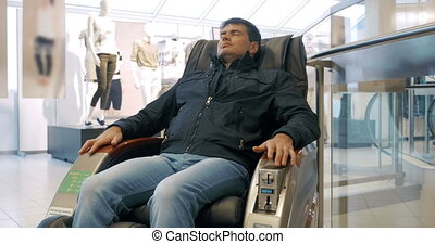 Rest in massage armchair after shopping - Man relaxing in...