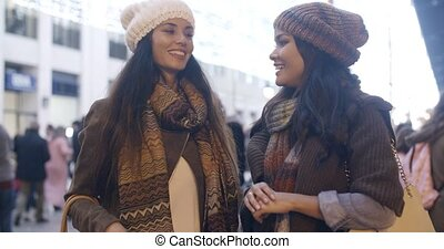 Two women chatting in a street in winter - Two stylish...