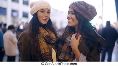 Two stylish young women in winter fashion standing outdoors...