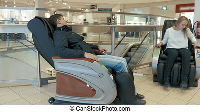 People in Massage Chairs in Trade Center - Man is resting in...