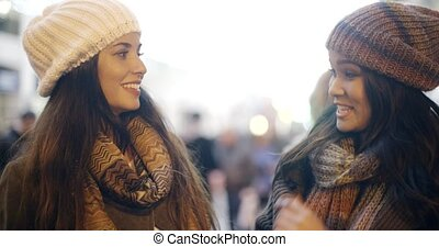 Two young woman enjoying a winter night out together as they...