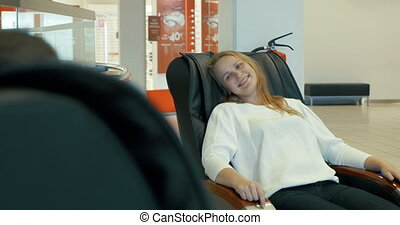 Young woman enjoying massage in special arm-chair