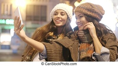 Two vivacious women taking a selfie - Two vivacious young...