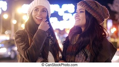 Two female friends enjoying a night on the town standing in...