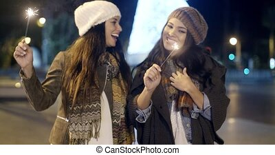 Two young women celebrating Christmas outdoors in winter in...
