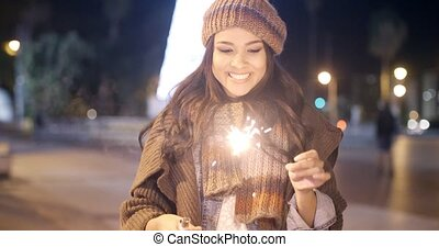 Pretty young woman celebrating with a sparkler - Pretty...