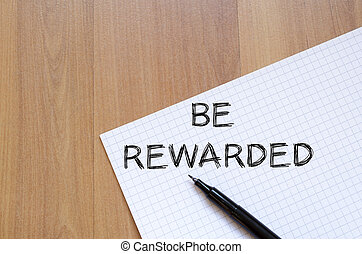 Be rewarded write on notebook - Be rewarded text concept...