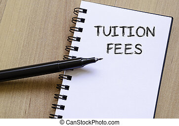 Tuition fees write on notebook - Tuition fees text concept...
