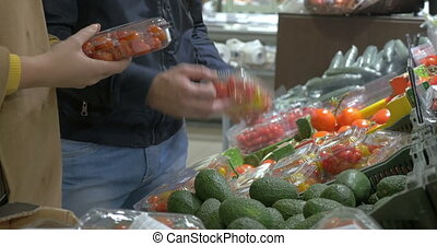 Customers choosing tomatoes in the supermarket