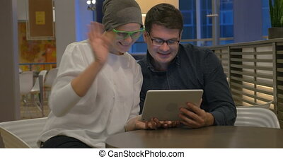 Man and woman using touch pad for video chatting - Young...