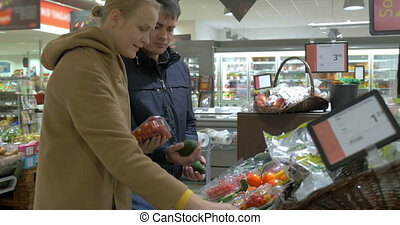Couple Choosing Vegetables in Supermarket - Young couple is...