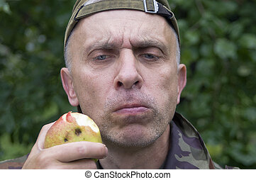 Man Chewing Food - Matured man chewing apple with a doubtful...